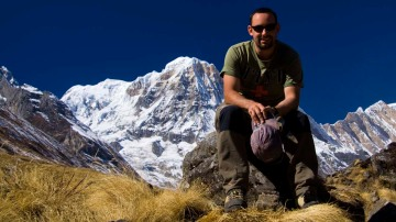 The blogger, sitting with Annapurna South (7,219m) in the background.  Annapurna Sanctuary, Nepal.