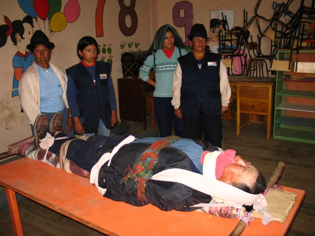 Community members, part of an emergency response committee in Ecuador, drill first-aid and casualty evacuation in preparation for a disaster event
